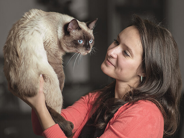 Woman holding up Cat