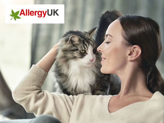 Allergy UK logo and cat on woman's shoulder