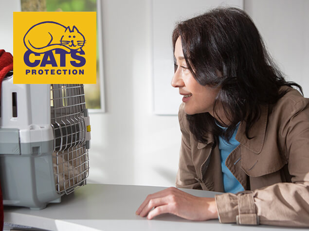 woman looking into cat carrier