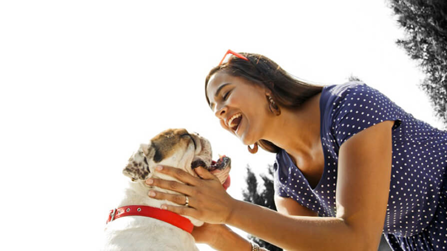 Woman holding her dog's head and smiling