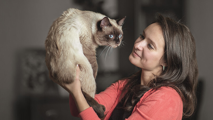 Woman holding her cat up